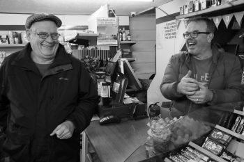 Two men sharing a joke in a village shop in Wales